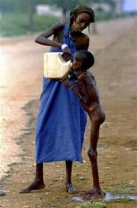 A starving Somali child is given water in Baidoa December 15, 1992. REUTERS/Yannis Behrakis